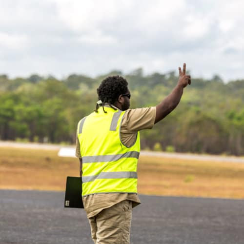 A man displaying the number two on a runway at the Iron Range Airport.