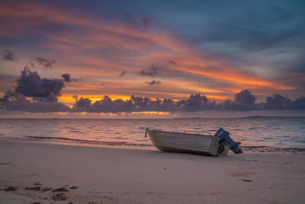 A small engine powered boat lies on the beach before the sunset.